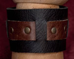 Wide cuff with a black base and a strip of brown riveted in with brass rivets and secured with snaps.